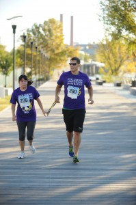 A woman and a man running in the 5K while holding a large rubber band or tether between them