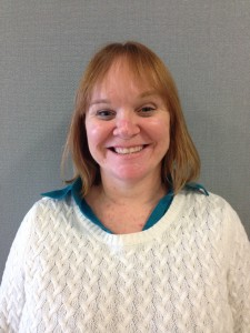Danyel Goldsmith is facing the camera with a head and shoulders portrait while wearing a white sweater.