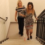 A woman learning to navigate stairs with a white cane