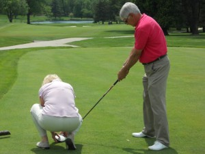 A coach assisting a blind golfer in lining up to the ball on a tee box