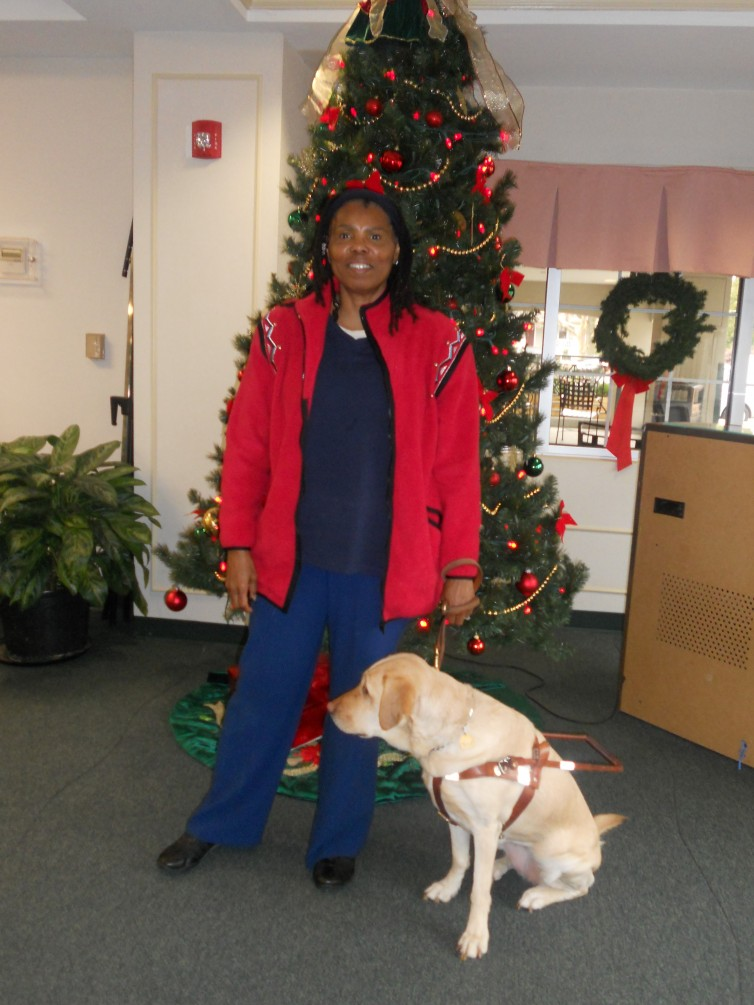 Woman & guide dog in front of a Christmas tree