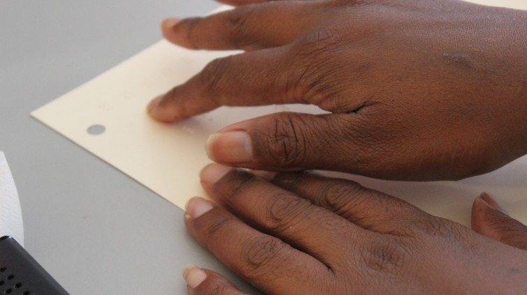 A closeup of a hand reading Braille