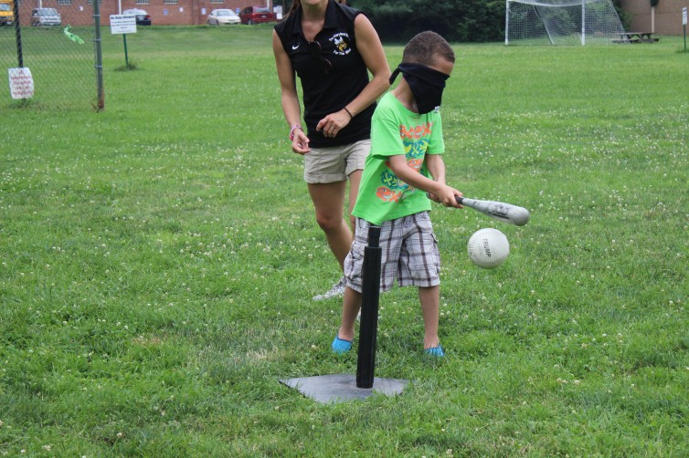 A child hitting a beepball off of a tee