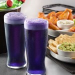 A photo of purple beer in a glass in front of food